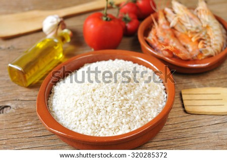 some ingredients to prepare a spanish paella or arroz negro, such as rice, tomato, garlic or shrimps, on a rustic wooden table - stock photo