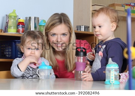 Some Kindergarten or nursery kids on a table drinking and playing 2 - stock photo