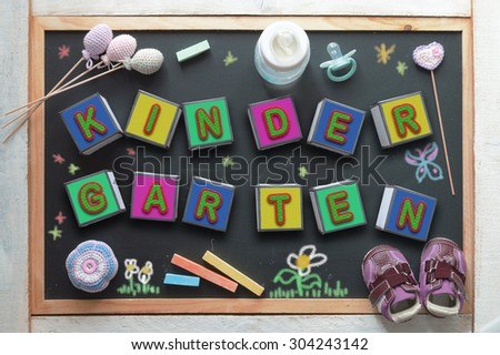 Some letter cubes forming the word kindergarten, a baby bottle, a pacifier, some toys and sneakers on a black chalkboard from above. Children education related objects. - stock photo