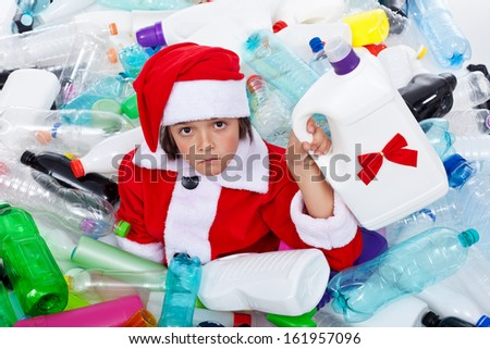 Some more plastic for this christmas - sad santa covered in plastic bottles waste - stock photo