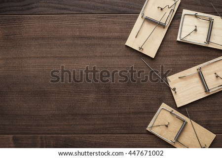 some mousetraps on the brown wooden background - stock photo