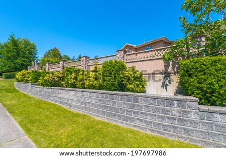 Some nicely trimmed bushes and fence on the leveled and stoned front yard. Landscape design. - stock photo