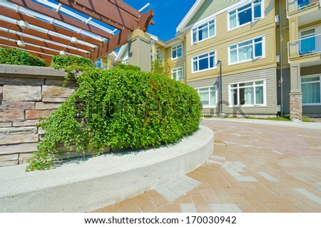 Some nicely trimmed bushes on the leveled and stoned bed on the paved plaza, court. Landscape urban design. - stock photo