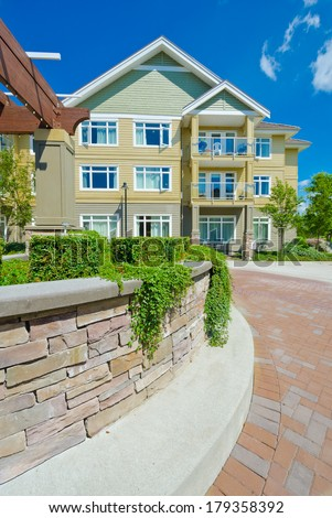 Some nicely trimmed bushes on the leveled and stoned bed on the paved plaza, court with townhouse. Landscape urban design. Vertical. - stock photo