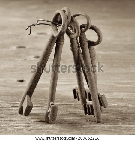 some old and rusty keys on a rustic wooden table, in sepia tone - stock photo