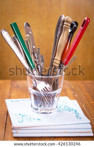 some old spoons and forks in glass on wooden background - stock photo