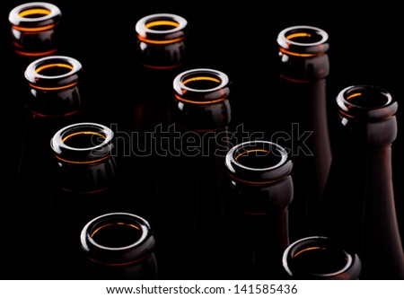 Some open beer bottles on a black background - stock photo