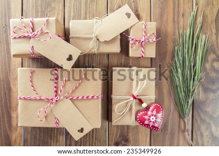 Some paper parcels wrapped tied with tags. A red heart and some christmas gift boxes wrapped with paper kraft and tied with red & white baker's twine on a wooden table. Vintage Style. - stock photo