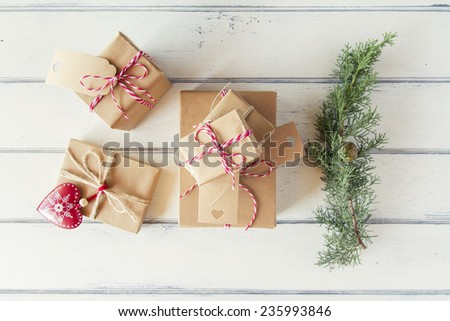 Some paper parcels wrapped tied with tags. A red heart and some christmas gift boxes wrapped with paper kraft and tied with red & white baker's twine on a white wooden table. Vintage Style. - stock photo