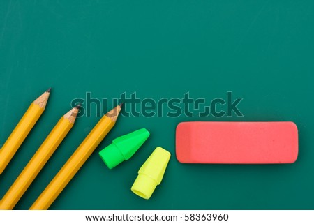 Some pencils and erasers on a chalkboard, back to school - stock photo
