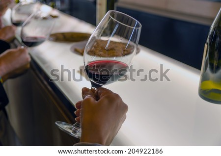 Some people are holding red wine cups in a wine tasting to see the wine transparency - stock photo