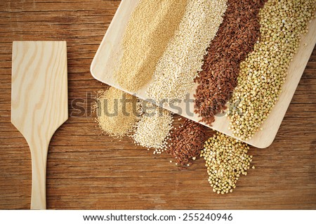 some piles of amaranth, quinoa, brown flax and buckwheat seeds on a rustic wooden table - stock photo