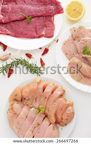 some plates with different raw meat such as turkey fillets, and chicken and beef meat, on a white table - stock photo
