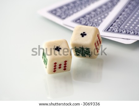 Some poker games: cards and dices, over a white reflecting table. - stock photo