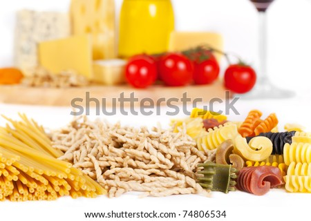Some popular kinds of the Italian pasta in the foreground and some kinds of the cheese, two glasses of wine, olive oil and tomatoes on a background. A shot horizontal, focus in the foreground. - stock photo