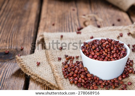 Some Red Beans (close-up shot) on rustic wooden background - stock photo