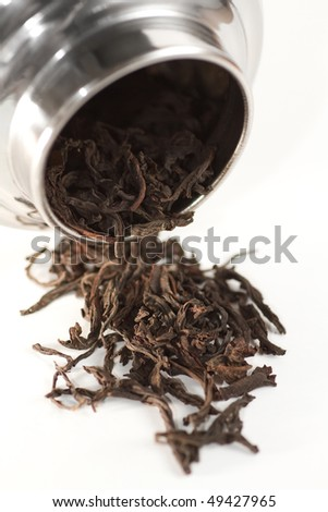 Some rolled Chinese tea leaves with a metal tea container on white background.