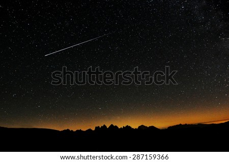 Some stars in the night with beautiful mountain before the sunrise at the Dolomiti. Real falling stars with darkness sky a the sunset - stock photo