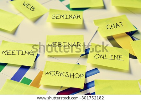 some sticky notes with work concepts, such as workshop, meeting, seminar, webinar, online, chat or web on an office desk full of charts - stock photo