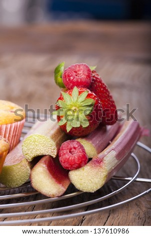 Some sweet fruits ingredients for muffins on a cake wire rack - stock photo