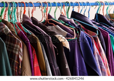 some used clothes hanging on a rack in a flea market - stock photo