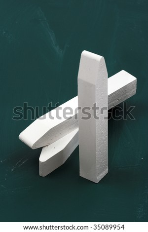 Some white chalk over green board,close up - stock photo