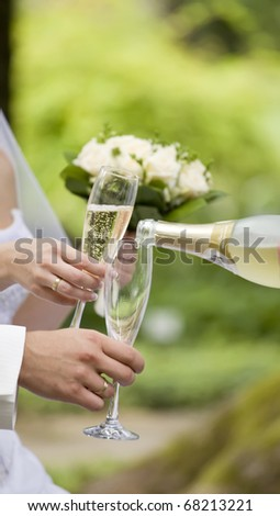 Somebody fills newly-married couple's glasses with champagne - stock photo