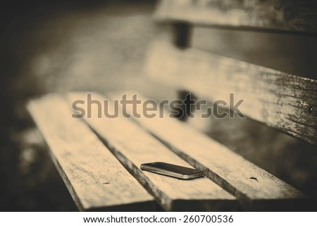 Someone forgot cell phone on a bench in the park - stock photo