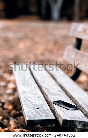Someone forgot cell phone on a bench in the park - lost phone on the bench - stock photo
