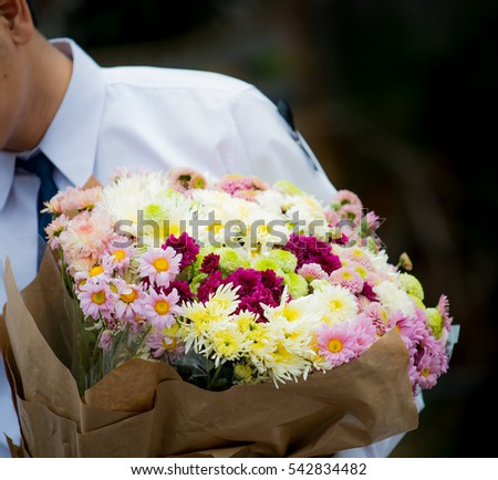 someone hold bouquet which have  many flowers , Closeup of beautiful fresh congratulation bouquet of colorful flowers pink violet lilac purple white orange and yellow in hands , horizontal picture