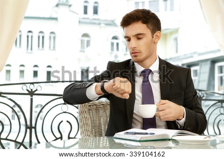 Someone is getting late. Businessman checking time on his watch while waiting for his colleague having a cup of coffee - stock photo