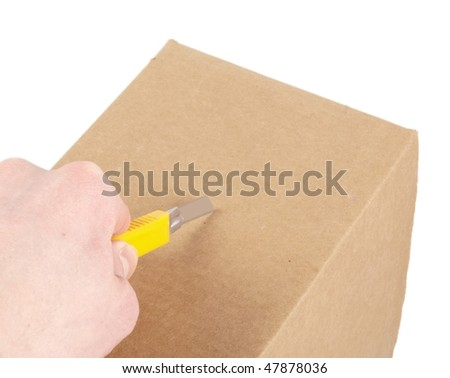 Someone is opening a big brown cardboard box with a knife