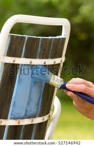 Someone is painting an old garden chair with nice blue color.