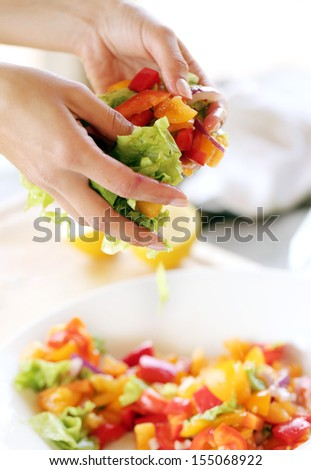 Someone is preparing a salad and is mixing the vegetables