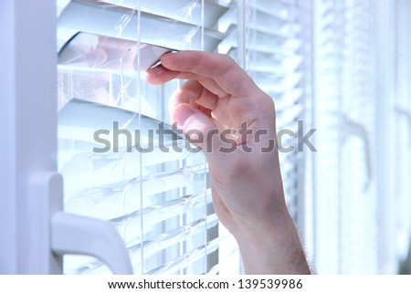 Someone looking out of window opening blinds - stock photo