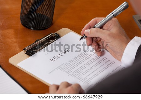 Someone looking over a submitted resume, or a person editing their own resume - stock photo