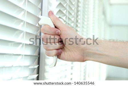 Someone opens metal-plastic window blinds closed - stock photo