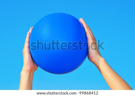someone playing with a blue beach ball - stock photo