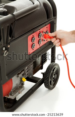 Someone plugging an extension cord into a portable gasoline generator. - stock photo