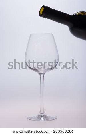 Someone wanted to pour red wine into empty glass standing on the white background - stock photo