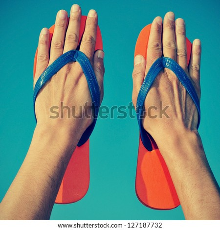 someone wearing flip-flops on his hands over the blue sky - stock photo