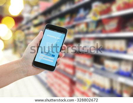someones  hand holding mobile smart phone with mobile shop  on supermarket blur background  - e-commerce concept - stock photo