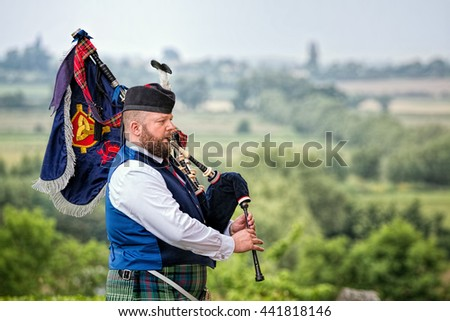 SOMERSET, UK - JUNE 20, 2016: Bagpiper plays bagpipes overlooking landscape. - stock photo