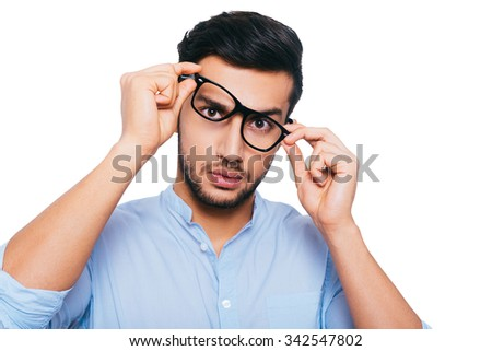 Something wrong with these eyeglasses. Frustrated young Indian man adjusting his eyeglasses while standing against white background - stock photo