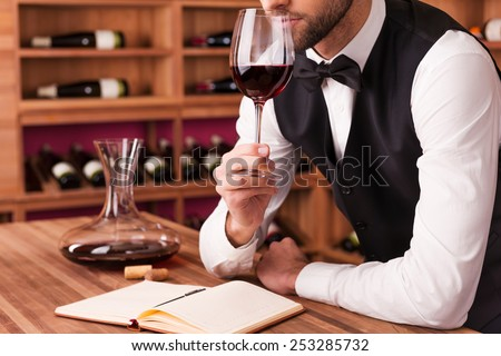 Sommelier examining wine. Cropped image of confident male sommelier examining wine while smelling it and leaning at the wooden table with wine shelf in the background  - stock photo