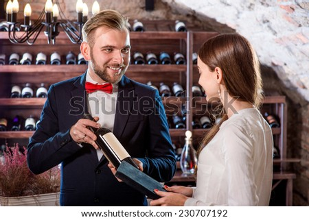 Sommelier showing wine bootle to woman in the wine cellar - stock photo