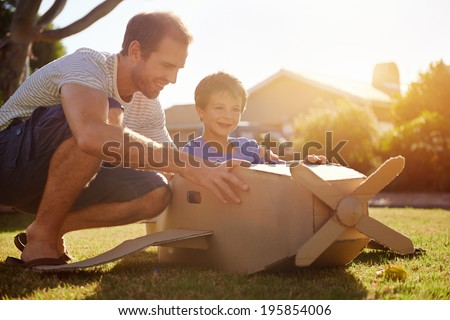 son and dad playing with toy aeroplane in the garden at home having fun together and smiling - stock photo