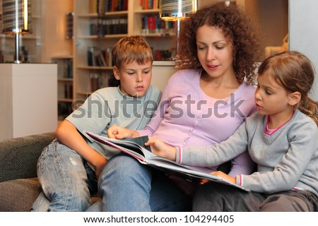 Son and daughter with their mother sit on sofa and read book in room; focus on woman