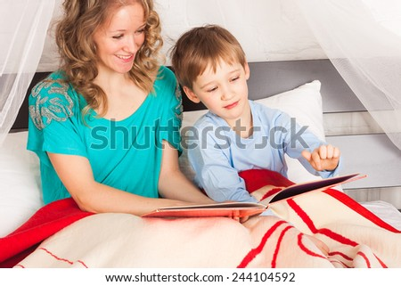 Son and his mother laying in bed and reading a book - stock photo