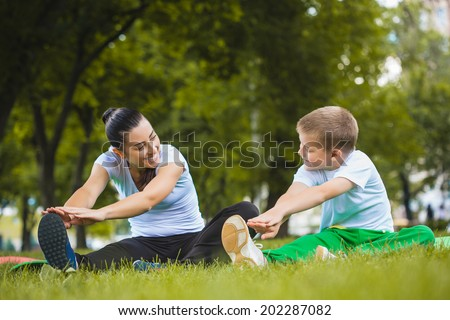 son and mother are doing exercises in the summer park - stock photo